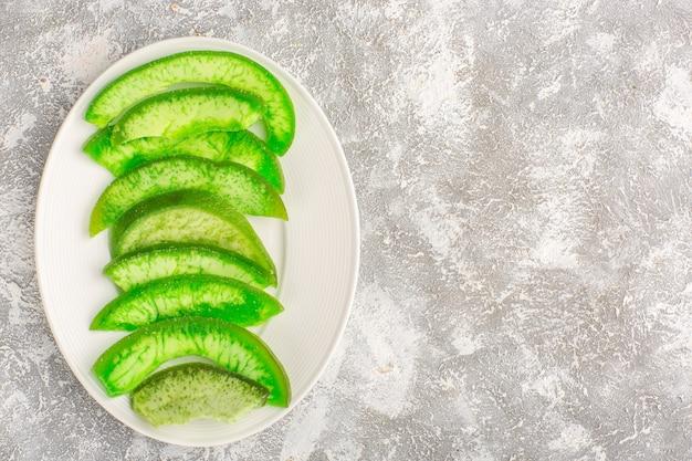 Bovenaanzicht gesneden groene komkommers binnen plaat op wit oppervlak
