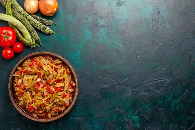 Bovenaanzicht gesneden groentemaal met verschillende ingrediënten binnen plaat op donkerblauwe achtergrond