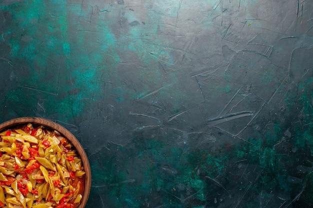 Bovenaanzicht gesneden groentemeel gekookt met verschillende ingrediënten op de donkerblauwe achtergrond