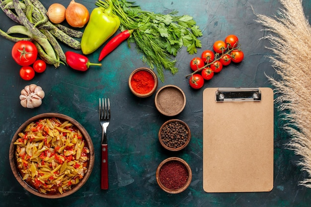 Bovenaanzicht gesneden groentemeel met verschillende ingrediënten en kruiden op donkerblauwe achtergrond