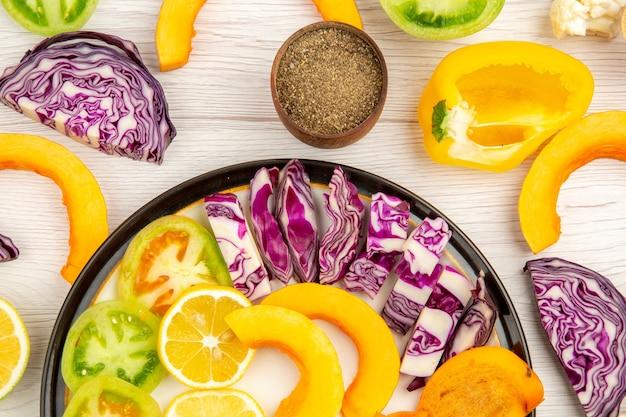 Bovenaanzicht gesneden groenten en fruit pompoen kaki rode kool citroen groene tomaten gele paprika op zwarte schotel zwarte peper in kom op tafel