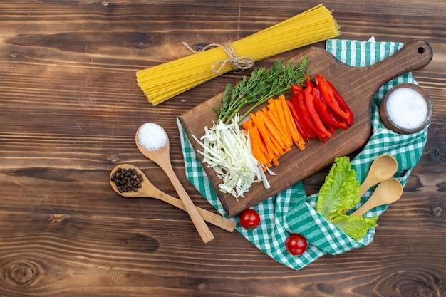 Bovenaanzicht gesneden groenten kool wortel greens en peper op snijplank bruin oppervlak