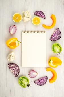 Bovenaanzicht gesneden groenten rode kool groene tomaat pompoen rode ui gele paprika bloemkool citroen notebook op wit houten oppervlak
