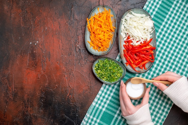 Bovenaanzicht gesneden groenten wortel kool en paprika met greens op donkere tafel