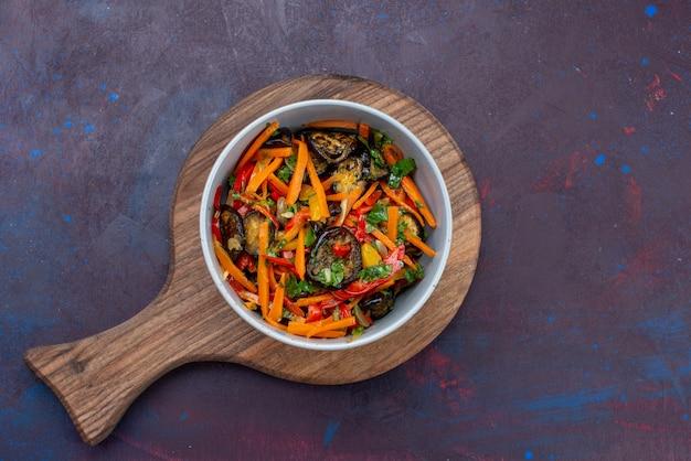 Bovenaanzicht gesneden groentesalade binnen plaat op de donkere groente van de het voedselmaaltijd van de bureausalade