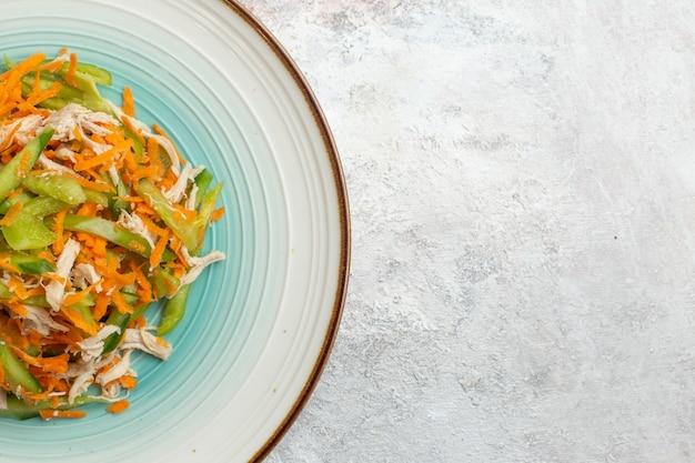 Bovenaanzicht gesneden groentesalade binnen plaat op lichte witte achtergrond
