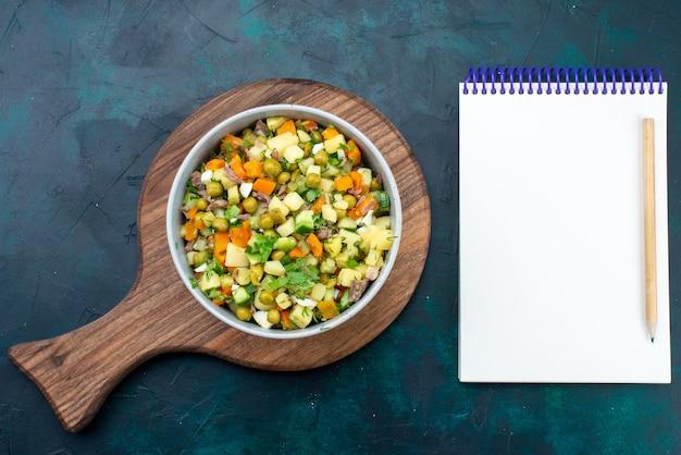 Bovenaanzicht gesneden groentesalade gepeperd met plakjes kip in plaat met blocnote op het donkerblauwe bureau