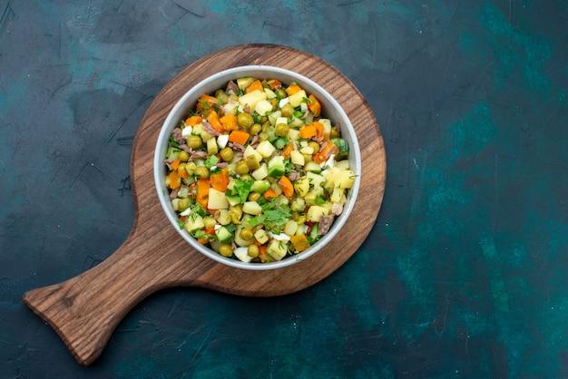 Bovenaanzicht gesneden groentesalade gepeperd met plakjes kip in plaat op het donkerblauwe bureau