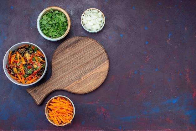 Bovenaanzicht gesneden groentesalade in plaat met greens op donker bureau
