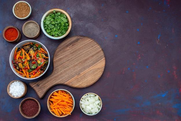 Bovenaanzicht gesneden groentesalade in plaat met kruidenkruiden op donker bureau