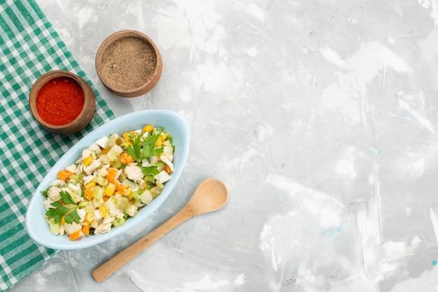Bovenaanzicht gesneden groentesalade met kippenplakken en kruiden op het witte plantaardige vlees van de de maaltijdschotel van het bureauvoedsel