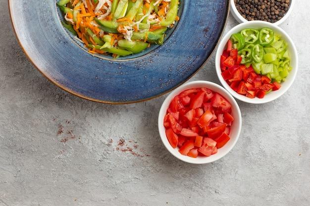 Bovenaanzicht gesneden groentesalade met kruiden op witte achtergrond