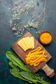 Bovenaanzicht gesneden kaas met gesneden gele paprika op donkerblauw bureau