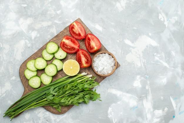 Bovenaanzicht gesneden komkommers en tomaten met zoutgreens en citroen op wit, salade plantaardig groen voedsel