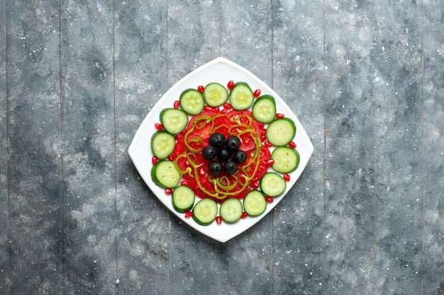 Bovenaanzicht gesneden komkommers met olijven in plaat op grijs bureau salade groente kleur vitamine gezondheid dieet
