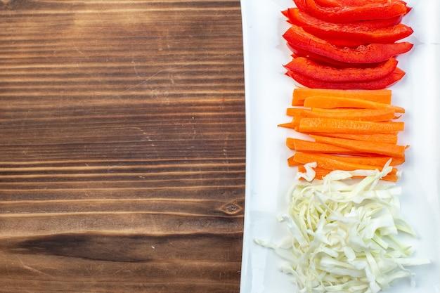 Bovenaanzicht gesneden kool met paprika op bruin oppervlak