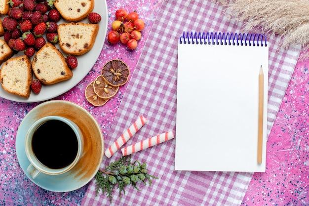 Bovenaanzicht gesneden lekkere taarten met koffienotitieblok en rode aardbeien op het lichtroze bureau