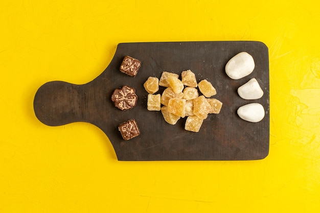 Bovenaanzicht gesneden marmelade zoete en suiker gesneden confitures met chocolade op geel oppervlak