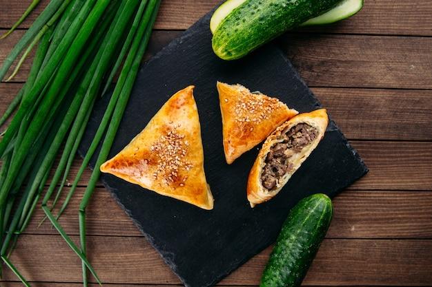 Bovenaanzicht gesneden oosterse schotel gebakken taart met vlees driehoek samsa op de zwarte stenen plaat