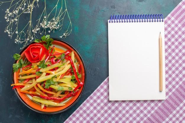 Bovenaanzicht gesneden paprika gekleurde pittige salade met blocnote op donkerblauw bureau