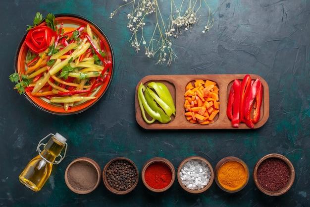 Bovenaanzicht gesneden paprika gezonde salade met olijfolie en kruiden op donkerblauw bureau