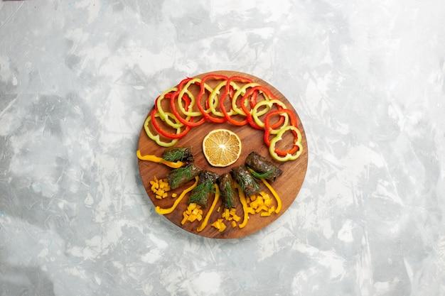 Bovenaanzicht gesneden paprika met blad dolma op wit bureau