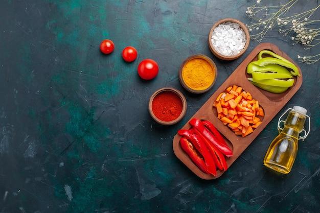 Bovenaanzicht gesneden paprika met kruiden en olie op de donkerblauwe achtergrond