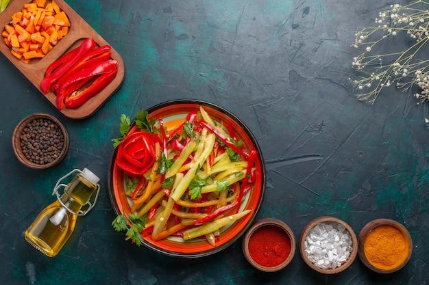 Bovenaanzicht gesneden paprika met kruiden salade en olie op blauwe achtergrond