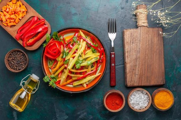 Bovenaanzicht gesneden paprika met kruiden salade en olie op donkerblauw bureau