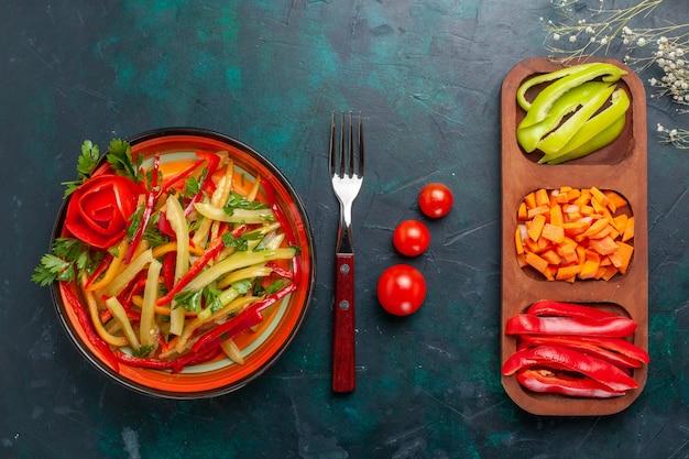 Bovenaanzicht gesneden paprika verschillende gekleurde groentesalade met ingrediënten op donkerblauwe achtergrond