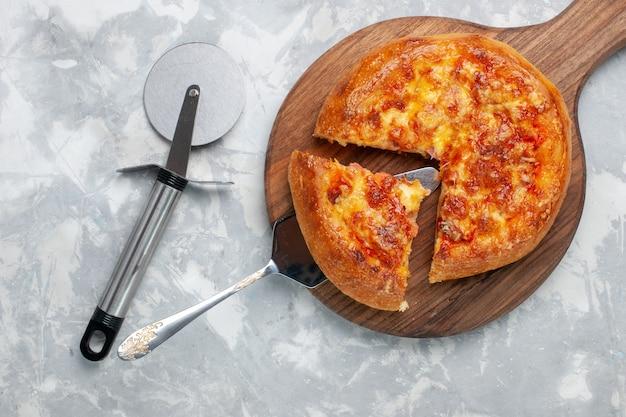 Bovenaanzicht gesneden pizza gebakken met kaas op wit