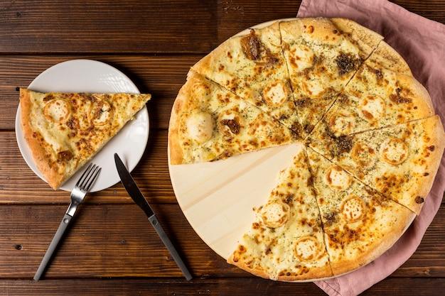 Bovenaanzicht gesneden pizza met kaas