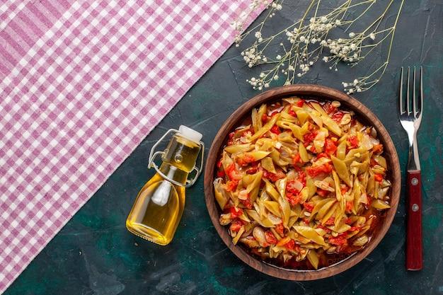 Bovenaanzicht gesneden plantaardige maaltijd heerlijke bonenmeel met olijfolie op de blauwe achtergrond
