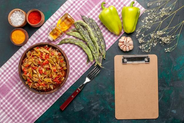 Bovenaanzicht gesneden plantaardige maaltijd met kruiden op donkerblauwe achtergrond