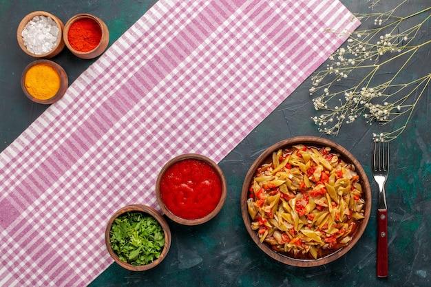 Bovenaanzicht gesneden plantaardige maaltijd met verschillende kruiden op de blauwe achtergrond