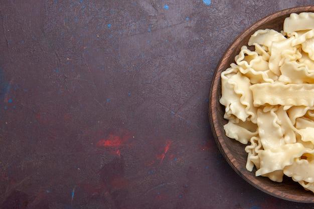 Bovenaanzicht gesneden rauw deeg binnen bruine plaat op donkere vloer maaltijd deeg eten pasta diner
