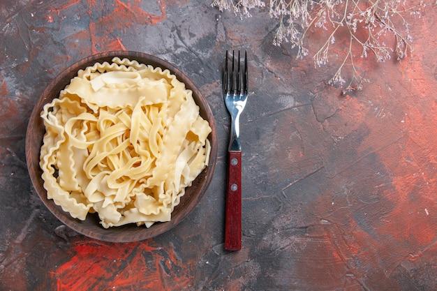 Bovenaanzicht gesneden rauw deeg binnen plaat op donkere ondergrond donker deeg pasta eten rauw