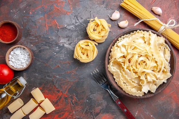 Bovenaanzicht gesneden rauw deeg binnen plaat op donkere oppervlak deeg pasta donker voedsel