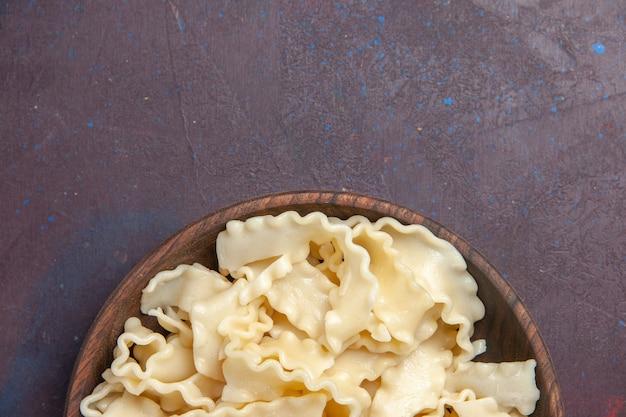 Bovenaanzicht gesneden rauw deeg in bruine plaat op donkere achtergrond maaltijd deeg eten diner pasta