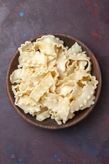 Bovenaanzicht gesneden rauw deeg in bruine plaat op donkere achtergrond maaltijd deeg eten pasta diner