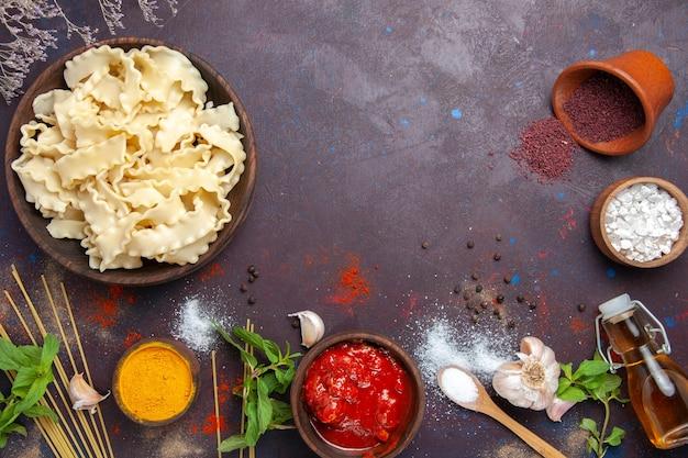 Bovenaanzicht gesneden rauw deeg met kruiden op donkere achtergrond deeg pasta maaltijd eten diner