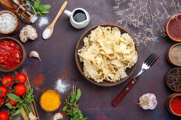 Bovenaanzicht gesneden rauw deeg met kruiden op donkere achtergrond maaltijd diner pastadeeg