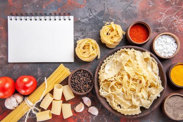 Bovenaanzicht gesneden rauw deeg met kruiden op donkere ondergrond pastadeeg donker voedsel