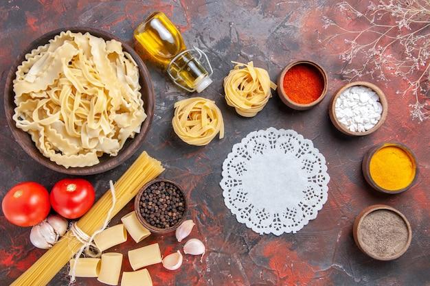 Bovenaanzicht gesneden rauw deeg met kruiden op donkere ondergrond pastadeeg donker