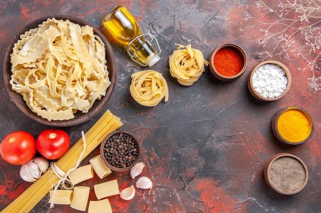Bovenaanzicht gesneden rauw deeg met kruiden op donkere vloer pastadeeg donker voedsel