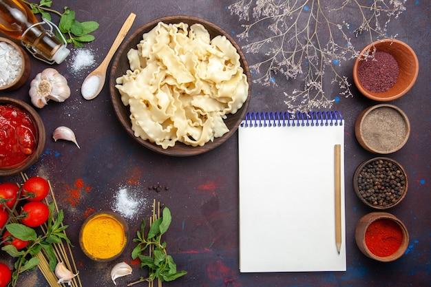 Bovenaanzicht gesneden rauw deeg met verschillende kruiden op donkere achtergrond maaltijd diner pasta deeg pittig