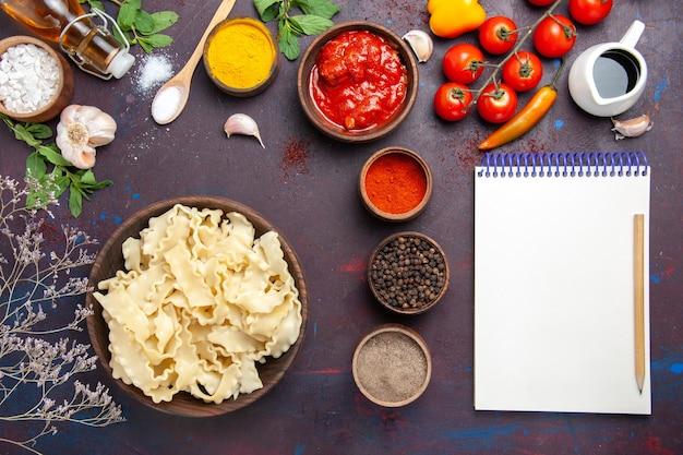 Bovenaanzicht gesneden rauw deeg met verschillende kruiden op donkere achtergrond maaltijd diner pastadeeg