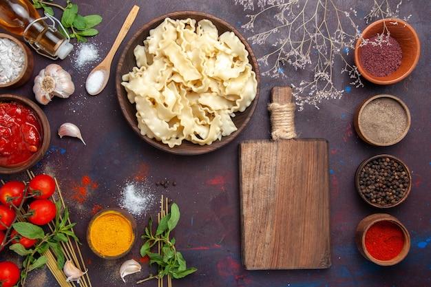 Bovenaanzicht gesneden rauw deeg met verschillende kruiderijen op donker bureau maaltijd diner pastadeeg