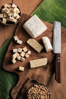 Bovenaanzicht gesneden rauwe tempeh snijden op houten snijplank boven rustieke bruine tafel met bananenblad