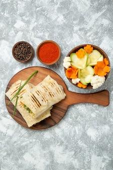Bovenaanzicht gesneden sandwich met groenten en kruiden op witte achtergrond brood maaltijd sandwich hamburger eten